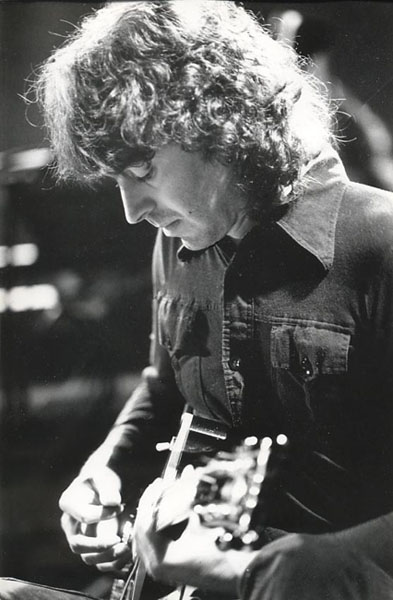 Richard playing electric guitar in concert